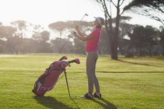 Pełna długość kobiety przewożenia kij golfowy Zdjęcia Royalty Free