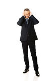 Pełna długość męczył mężczyzna nakrywkowych ucho z rękami Fotografia Stock