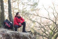 Pełna długość męski wycieczkowicza przycupnięcie na falezie w lesie Obrazy Stock