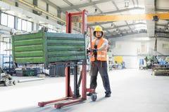Pełna długość młoda ręcznego pracownika dosunięcia ręki ciężarówka z ciężkim metalem w przemysle Zdjęcie Royalty Free