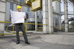 Pełna długość młody męski architekt egzamininuje projekt na zewnątrz przemysłu Zdjęcie Stock