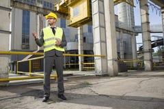 Pełna długość młody męski architekt gestykuluje na zewnątrz przemysłu Zdjęcie Stock