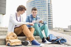 Pełna długość młodzi męscy studenci collegu studiuje na krokach przeciw budynkowi Obrazy Stock
