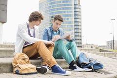 Pełna długość młodzi męscy studenci collegu studiuje na krokach przeciw budynkowi Obraz Stock
