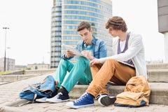 Pełna długość młodzi męscy studenci collegu studiuje na krokach przeciw budynkowi zdjęcia stock