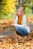 Pełna długość rozważny młodej kobiety przycupnięcie na krokach w parku Fotografia Stock