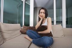 Pełna długość sprężająca młodej kobiety mienia poduszka na kanapie w żywym pokoju fotografia royalty free