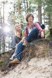 Pełna długość wycieczkować pary obsiadanie na krawędzi faleza w lesie Zdjęcie Royalty Free