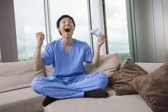 Pełna długość z podnieceniem w połowie dorosły mężczyzna bawić się wideo grę w żywym pokoju fotografia royalty free