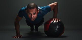 pełna energii Młody sportowiec robi Ups z piłką nad ciemnym tłem obrazy royalty free