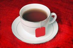 Pełna herbaciana filiżanka na czerwonym tle Zdjęcia Royalty Free