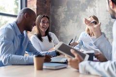 Pełna koncentracja przy pracą Grupa młodzi ludzie biznesu pracuje i komunikuje podczas gdy siedzący przy biurowym biurkiem obrazy stock