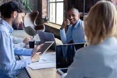 Pełna koncentracja przy pracą Grupa młodzi ludzie biznesu pracuje i komunikuje podczas gdy siedzący przy biurowym biurkiem obraz stock