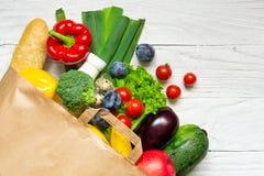 Pełna papierowa torba różny zdrowia jedzenie na białym drewnianym tle fotografia stock