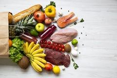 Pełna papierowa torba zdrowy surowy jedzenie na białym drewnianym stole Kulinarny karmowy tło Lay świeże owoc, veggies, zielenie, zdjęcie stock