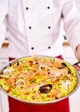 Pełna porcja niosąca szefem kuchni makaronu paella obrazy stock