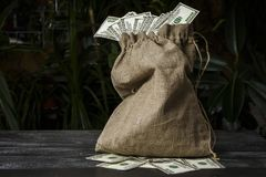Pełna torba dolary na zmroku stole fotografia royalty free