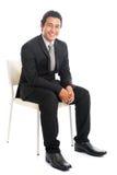 Pełnego ciała biznesmena Azjatycki obsiadanie na białym krześle zdjęcie stock