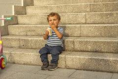 Pełnego strzału portreta śliczna chłopiec ma przekąskę siedzi w kamiennym sta Zdjęcia Stock