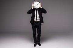 Pełnego wzrosta przystojny mężczyzna w szarość nadaje się trzymający dużego zegarowego nakrycie jego twarz Obraz Royalty Free