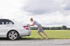 Pełnej długości boczny widok bizneswomanu puszka dosunięcie łamający samochód przy wsią obraz royalty free