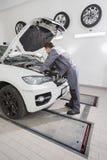 Pełnej długości boczny widok męski samochodu mechanik naprawia samochodowego silnika w remontowym sklepie Zdjęcie Stock