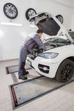 Pełnej długości boczny widok męski samochodu mechanik naprawia samochodowego silnika w remontowym sklepie Zdjęcie Royalty Free