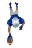 Pełnej długości tylni widok futbolu amerykańskiego gracza dojechanie w kierunku piłki Zdjęcie Stock