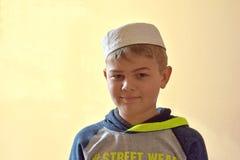 Pełnej twarzy portreta wizerunek młoda śliczna muzułmańska chłopiec jest ubranym tradycyjną islamską modlitewną kapeluszową nakrę Obrazy Stock