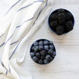 Pełni błękitni puchary jagody na białym drewnianym tle, zasięrzutny widok Od above, odgórny widok fotografia stock
