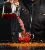 Pełnia w górę - mężczyzna nalewa napój od dzbanka w szklaną filiżankę, ty możesz widzieć krople i ciekłego pluśnięcie zdjęcie stock