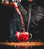 Pełnia w górę - mężczyzna nalewa napój od dzbanka w szklaną filiżankę, ty możesz widzieć krople i ciekłego pluśnięcie obrazy stock