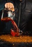 Pełnia w górę - mężczyzna nalewa napój od dzbanka w szklaną filiżankę, ty możesz widzieć krople i ciekłego pluśnięcie fotografia stock