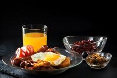 Pełny Angielski śniadanie z rozdrapanymi jajkami, bekonem, kiełbasą, fasolami, pomidorami i sokiem, Zdjęcia Royalty Free