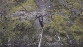 Pełny ciało strzał młoda kobieta krzyżuje drucianego most nad Nevis rzeką, Szkocja zbiory