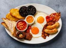 Pełny dłoniak w górę Angielskiego śniadania z smażącymi jajkami, kiełbasy, bekon zdjęcia stock