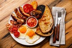 Pełny dłoniak w górę Angielskiego śniadania z smażącymi jajkami, kiełbasy, bekon obraz royalty free
