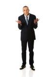 Pełny długość biznesmen robi niezdecydowanemu gestowi Obrazy Royalty Free