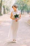 Pełny długość portret jeden piękna zmysłowa młoda panna młoda w lekkiej biel sukni i pozować przy parkowym mienie ślubem zdjęcia stock