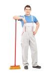 Pełny długość portret męski cleaner trzyma miotłę Obrazy Royalty Free