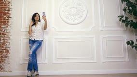 Pełny długość portret młoda kobieta, dziewczyna, brunetka, w białej koszula i cajgach stoi na tle biel ściana z, zbiory wideo