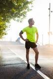 Pełny długość portret odpoczywa po treningu outdoors męski biegacz podczas gdy cieszący się pięknego wschód słońca w lato ranku Obraz Royalty Free