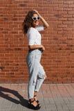Pełny długość portret piękna śliczna młoda kobieta z długim kędzierzawym włosy w białej koszulce obraz stock