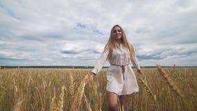 Pełny długość portret piękna młoda szczęśliwa kobieta w białym smokingowym bieg przez pszenicznego pola zbiory