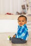 Pełny długość portret potomstwo mieszający biegowy chłopiec obsiadanie na podłoga obraz royalty free