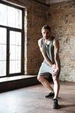 Pełny długość portret skoncentrowany sportowiec robi rozciąganiu ćwiczy zdjęcie stock
