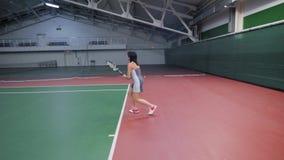 Pełny długość portret szczupła seksowna kobieta w sporta stroju bawić się tenisa przy salowym sądem z fachowym wyposażeniem zbiory