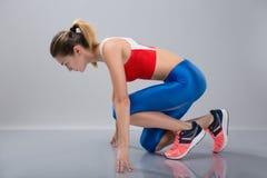 Pełny długość portret ufna skupiająca się sportsmenka dostaje przygotowywający zaczynać biegać podczas gdy pozujący zdjęcie royalty free