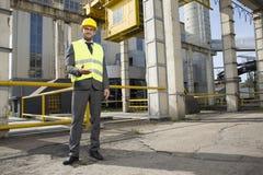 Pełny długość portret ufny męski inżynier gestykuluje na zewnątrz przemysłu Zdjęcia Stock