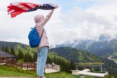 Pełny długość profilu strzał piękna młoda kobieta z flagą amerykańską trzymającą w jej szeroko rozpościerać ręki pozycji przed tu obrazy stock